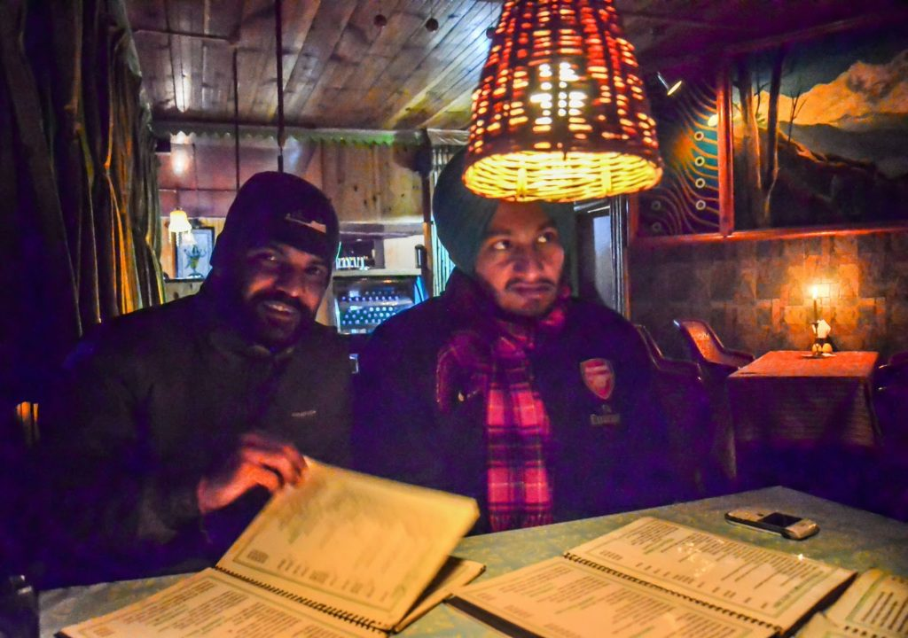 Checking the menu at Evergreen Restaurant in Kasol